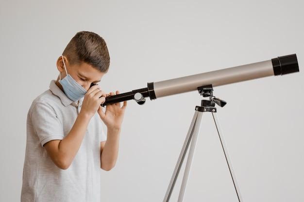 Zijaanzichtjongen die leert hoe hij een telescoop moet gebruiken