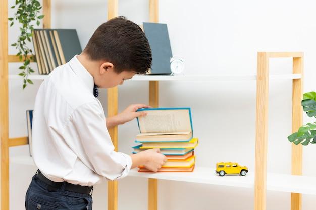 Zijaanzichtjongen die stapel boeken controleren