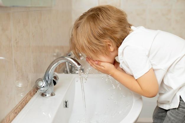 Zijaanzichtjongen die zijn gezicht wast