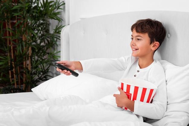 Zijaanzichtjongen in bed met afstandsbediening en popcorn