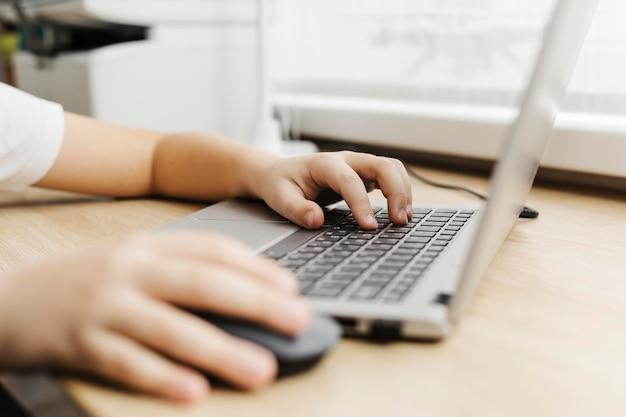 Zijaanzichtkind dat laptop met behulp van