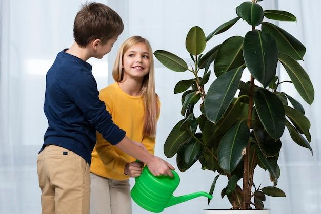 Zijaanzichtkinderen die samen bloem water geven