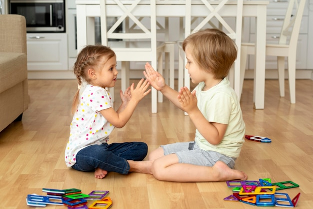 Zijaanzichtkinderen die thuis met speelgoed spelen