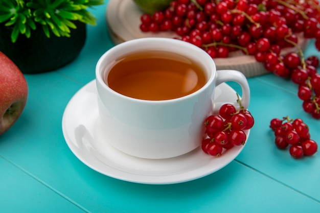Zijaanzichtkop thee met rode aalbessen met appelen op een lichtblauwe achtergrond