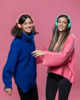 Zijaanzichtmama en dochter het luisteren muziek