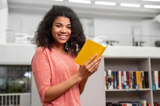 Zijaanzichtmeisje dat bij bibliotheek bestudeert