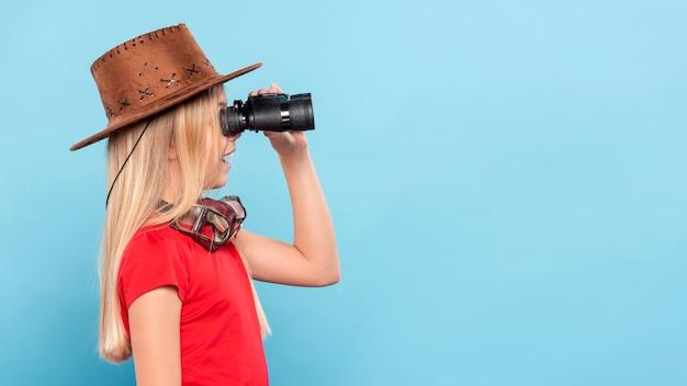 Zijaanzichtmeisje dat met binoculair kijkt