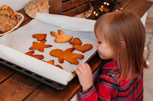 Zijaanzichtmeisje die gebakken kerstmiskoekjes controleren