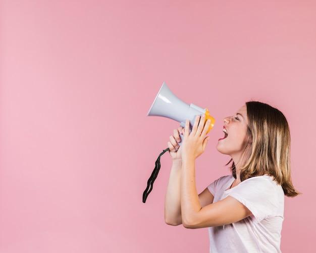 Zijaanzichtmeisje die op een megafoon gillen