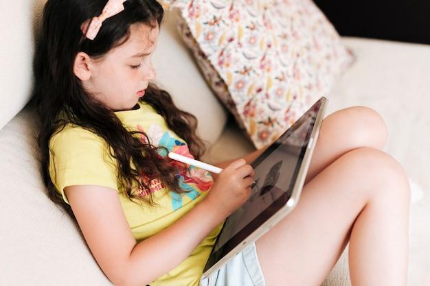 Zijaanzichtmeisje die op een tablet trekken