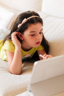 Zijaanzichtmeisje die op haar tablet letten