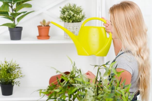 Zijaanzichtmeisje het water geven bloemen
