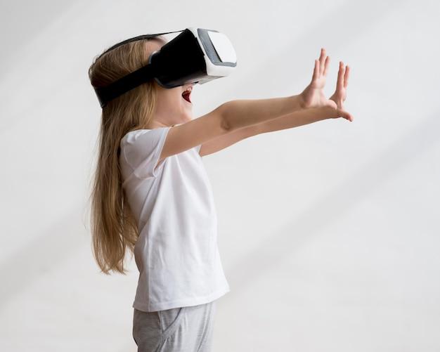 Zijaanzichtmeisje met virtuele werkelijkheidshoofdtelefoon
