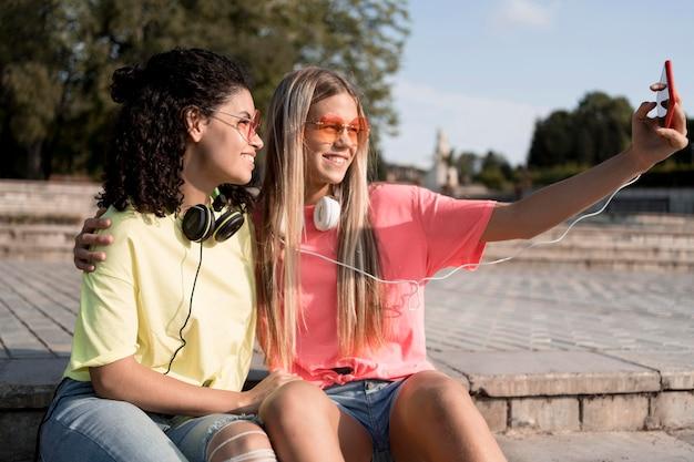 Zijaanzichtmeisjes die selfies buitenshuis nemen