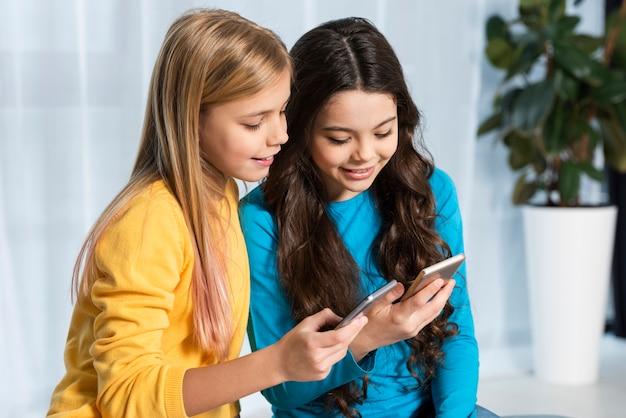 Zijaanzichtmeisjes met mobiel