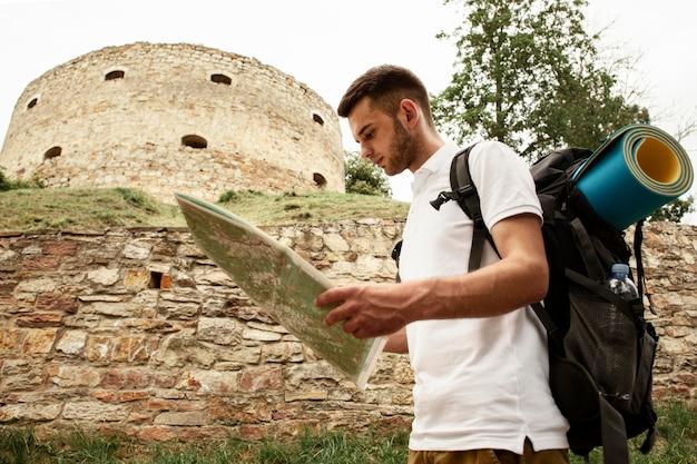 Zijaanzichtmens bij kasteelruïnes met kaart