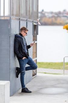 Zijaanzichtmens die aan muziek op oortelefoons buiten luisteren