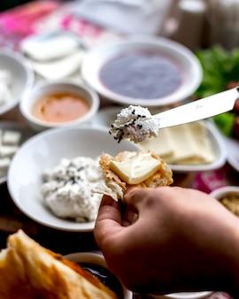 Zijaanzichtmens die boter met brood en kwark met papaverzaden eet