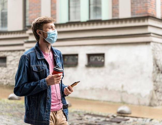 Zijaanzichtmens die een medisch masker buiten met exemplaarruimte draagt