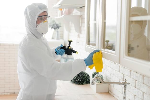 Zijaanzichtmens die keuken desinfecteert