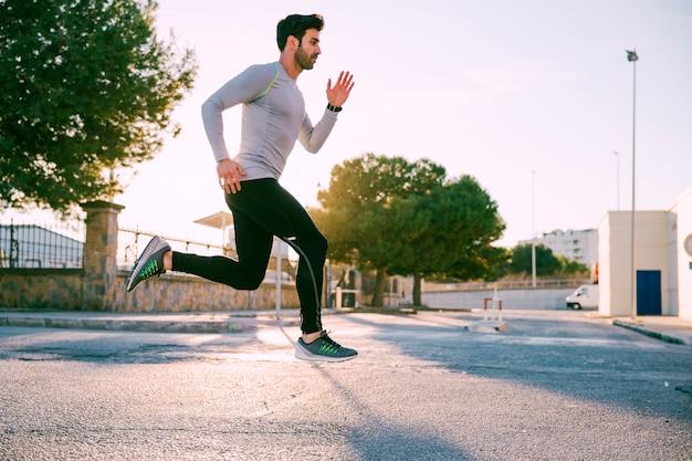 Zijaanzichtmens die op straat springt