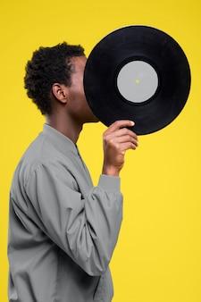 Zijaanzichtmens die zijn gezicht bedekt met een vinylplaat terwijl hij ultieme grijze kleding draagt