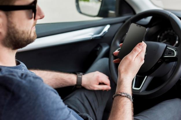 Zijaanzichtmens die zijn smartphone in zijn auto controleert