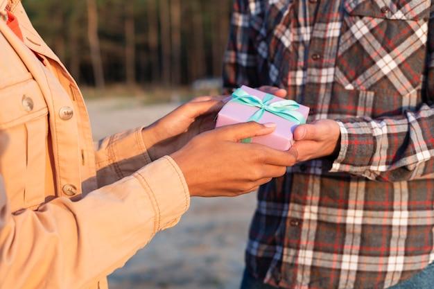 Zijaanzichtmens die zijn vriendin een ingepakt geschenk geeft