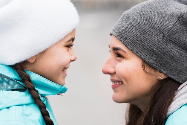 Zijaanzichtmoeder en dochter die elkaar bekijken