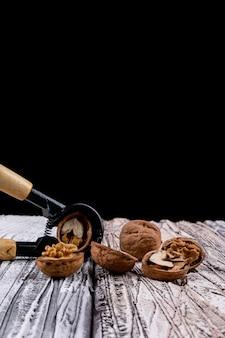 Zijaanzichtnotekraker en okkernoten op houten lijstverticaal