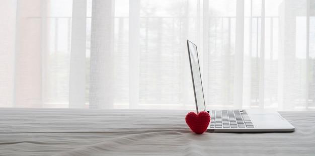 Zijaanzichtnotitieboekje, laptop en rood hartvormig symbool op bed in slaapkamer.