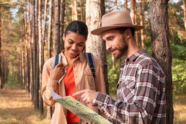 Zijaanzichtpaar controleert een kaart voor een nieuwe bestemming