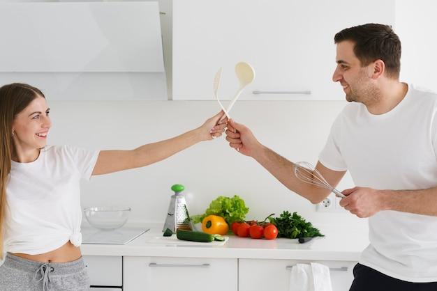 Zijaanzichtpaar die terwijl het koken spelen