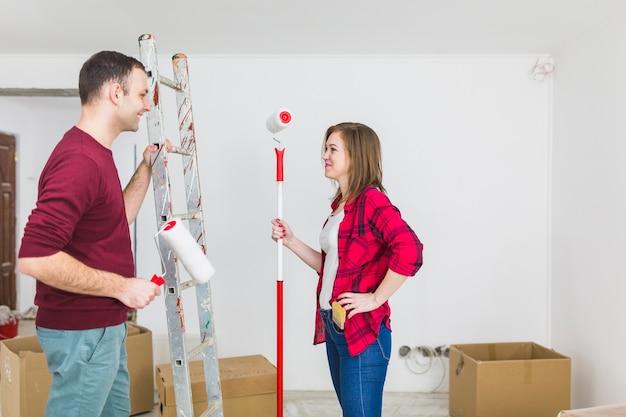 Zijaanzichtpaar met verfrollen en ladder