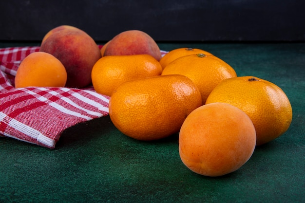 Zijaanzichtperziken met mandarijnen en abrikozen op keukenhanddoek