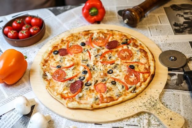 Zijaanzichtpizza op een dienblad met tomaten en gekleurde paprika's op een krant