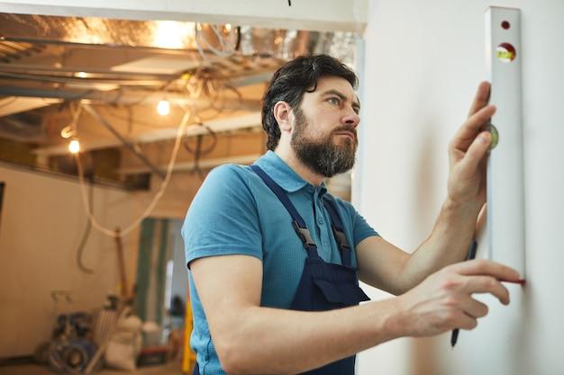 Zijaanzichtportret van bebaarde bouwvakker die niveau van muur meet tijdens het renoveren van huis, exemplaarruimte