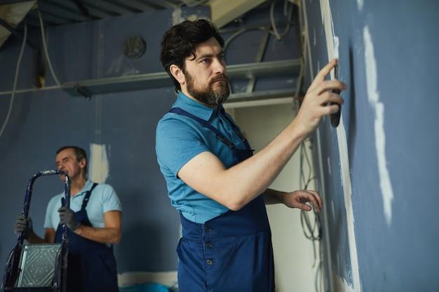 Zijaanzichtportret van bebaarde man die aan droge muur werkt tijdens het renoveren van huis, exemplaarruimte