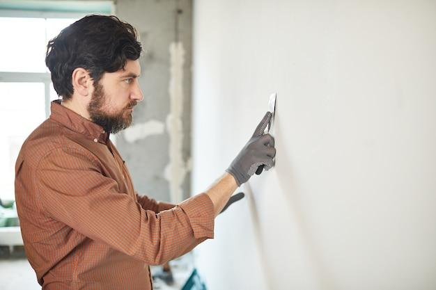 Zijaanzichtportret van bebaarde man die witte muur met spatel gladstrijkt tijdens het renoveren van huis, exemplaarruimte