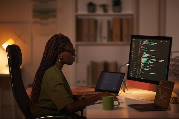 Zijaanzichtportret van de eigentijdse afro-amerikaanse vrouw die code schrijft en naar het computerscherm kijkt tijdens het werken in een schemerig kantoor, kopieer ruimte