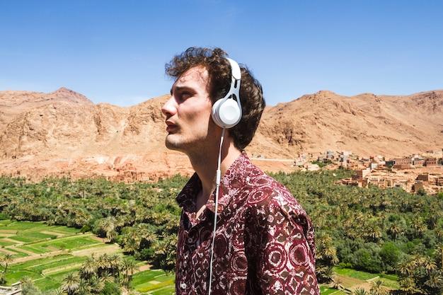 Zijaanzichtportret van de jonge mens die aan muziek in oase luisteren