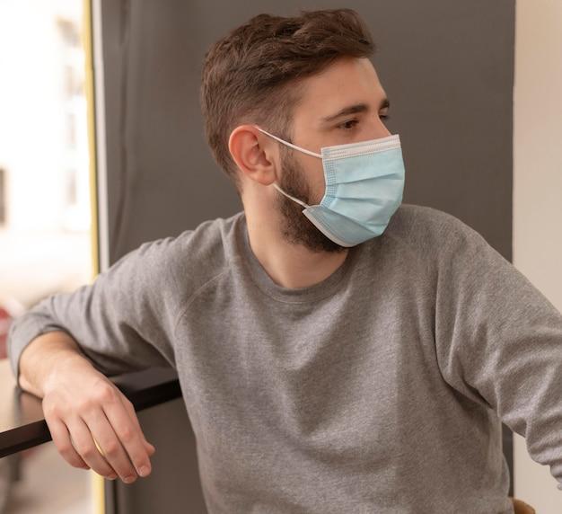 Zijaanzichtportret van de jonge mens die een medisch masker draagt