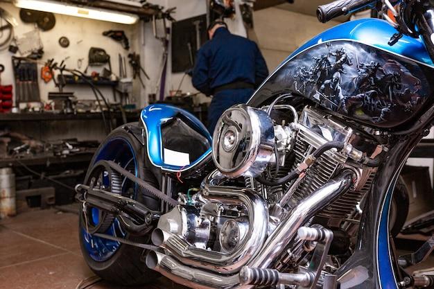Zijaanzichtportret van de mens die in garage werkt die motorfiets herstelt en het aanpast