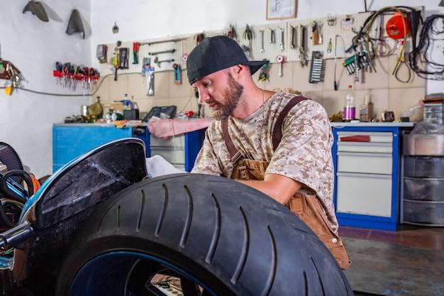 Zijaanzichtportret van de mens die in garage werkt die motorfiets herstelt