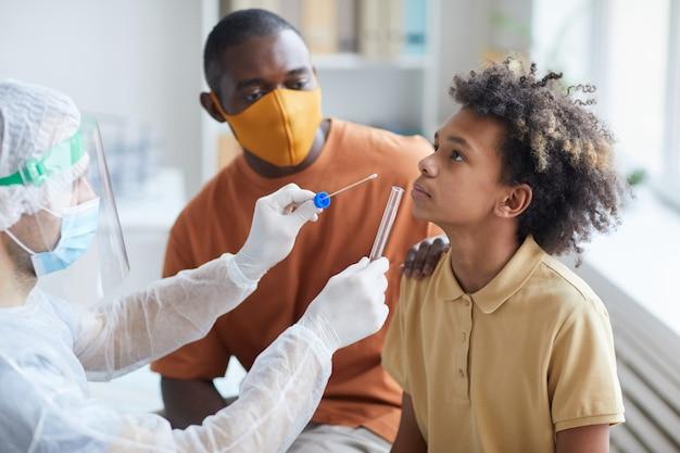 Zijaanzichtportret van een afro-amerikaanse tienerjongen die covid-test doet in de kliniek met een verpleger die een wattenstaafje en een glazen buis vasthoudt