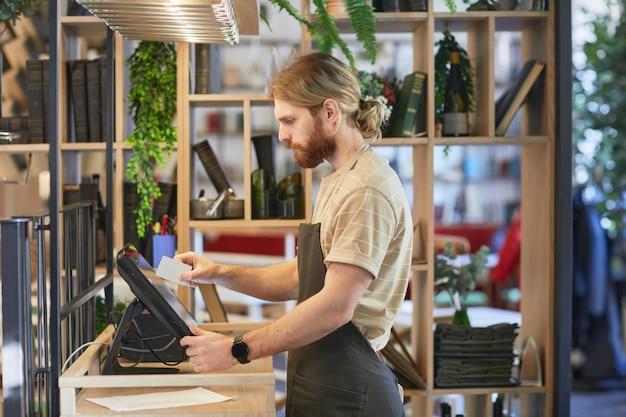 Zijaanzichtportret van een bebaarde cafémedewerker die een register gebruikt tijdens het verwerken van bestellingen in een groen, milieuvriendelijk interieur, kopieerruimte