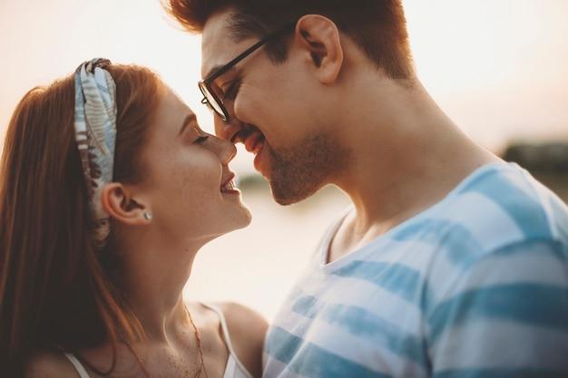 Zijaanzichtportret van een charmant jong paar dat alvorens te kussen tijdens het daten in het park bij de zonsondergang lacht.