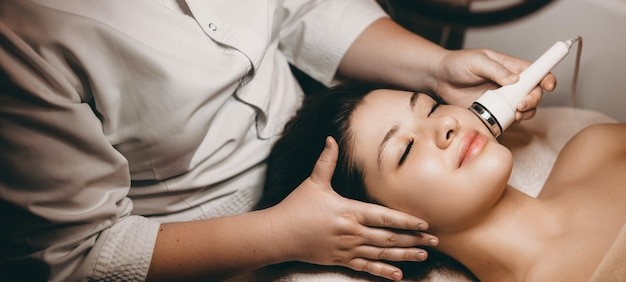 Zijaanzichtportret van een charmante vrouw die een elektroporatieprocedure op haar gezicht doet tijdens het schoonmaken met gesloten ogen op een kuuroordbed in welens kuuroord.