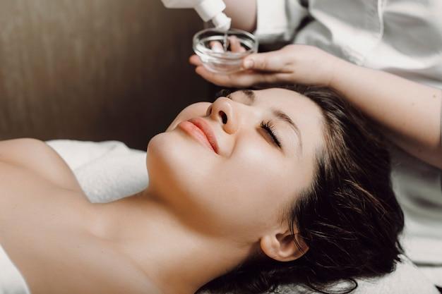 Zijaanzichtportret van een charmante vrouw die op een kuuroordbed leunt met gesloten ogen met gezichtshuidverzorgingsmasker in een wellnesscentrum.