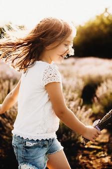 Zijaanzichtportret van een gelukkig kind dat op een biobloemgebied speelt tegen zonsondergang het lachen.